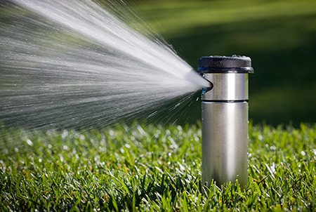 Oahu Sprinkler Services Image of a sprinkler watering a lawn